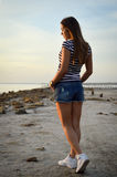 Beautiful girl walking on rocky beach  watching Stock Photography