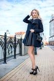 Beautiful girl walking in the street of city. Beautiful young woman wearing fashion black dress walking in the street of the city. Coat and high heeled shoes Royalty Free Stock Photography