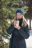 Beautiful girl walking in winter city park with a bag and drink Royalty Free Stock Image