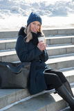 Beautiful girl walking in winter city park with a bag and drink Royalty Free Stock Photo