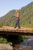 Beautiful girl walking on a wooden bridge. Beautiful girl in sportswear walking on a wooden bridge in the mountain Stock Photo