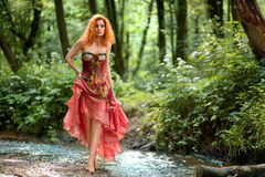 Beautiful girl walking in the woods. Fairy girl with red hair in a red dress walking in the forest on the water Stock Images
