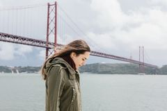 A beautiful girl walks alone along the shore near the bridge in Lisbon. royalty free stock photography