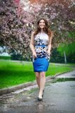 Beautiful girl walks in blooming garden, spring Royalty Free Stock Photos