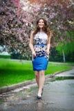 Beautiful girl walks in blooming garden, spring Royalty Free Stock Photos