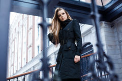 Beautiful girl walks through the city. Beautiful girl in a black coat walking in the city Royalty Free Stock Image