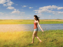 Beautiful girl walks on the grass. Against the background of the river and the light from the sun Royalty Free Stock Photos