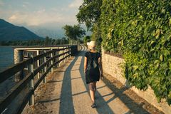 The beautiful girl walks on Lake Como on a summer day. royalty free stock photography