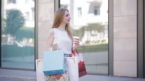 A beautiful girl walks with packages from the store and drinks coffee. Successful shopping. stock footage