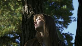 A beautiful girl wanders through the forest. The girl was lost. In the background, the sky. A beautiful girl wanders through the forest. The girl was lost. In stock footage