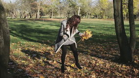 Beautiful girl in warm coat collecting yellow leaves in the park. stock video footage