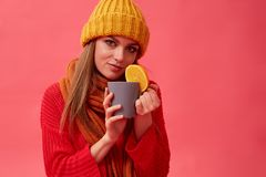 Beautiful girl in warm cozy sweater holds a hot drink with orange. Red background. Studio. Woman in warm cozy sweater holds a hot drink with orange. Red royalty free stock photos