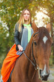 A beautiful girl was walking her horse. Focus on the horse. The warm tone of the image. Soft focus. Royalty Free Stock Photography
