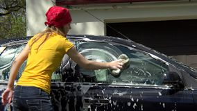 Beautiful girl washes her car with sponge. stock footage