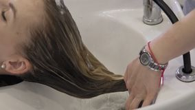 Beautiful girl washes her hair before haircut in beauty salon. Hair washing stock footage