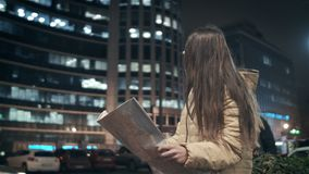 A beautiful girl is watching a map at night in the city on a building background. Asks the passerby how to find the. Street. Lost stock video footage