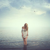 Beautiful girl in the water. Beach, sunrise, cold Stock Images