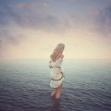 Beautiful girl in the water. Beach, sunset, Royalty Free Stock Image