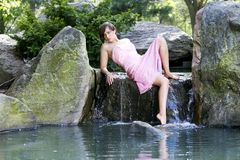 Beautiful girl by the water on a rock Stock Photos