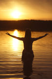 Beautiful girl in water on sunset Stock Photography
