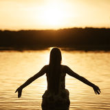 Beautiful girl in water on sunset Royalty Free Stock Images