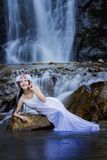 Beautiful girl with waterfall. Beautiful girl playing with waterfall,A portrait of a beautiful asian woman smiling brightly at the camera Stock Photo