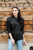 Rock style beautiful european young woman. Pretty girl in a leather jacket. Woman beauty face portrait. Beautiful girl with wavy hair in black leather jacket stock images