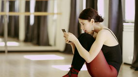 Beautiful girl wearing ballet leotard with cellphone. Beautiful brunette girl wearing ballet leotard sitting on the floor with cellphone indoor stock video