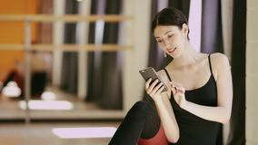 Beautiful girl wearing ballet leotard with cellphone. Beautiful brunette girl wearing ballet leotard sitting in a beautiful pose on the floor with cellphone stock footage