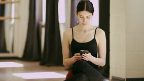 Beautiful girl wearing ballet leotard with cellphone. Beautiful brunette girl wearing ballet leotard sitting in a beautiful pose on the floor with cellphone stock video