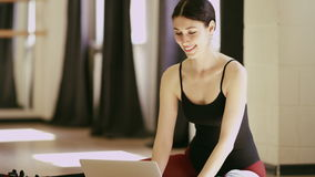 Beautiful girl wearing ballet leotard with laptop. Beautiful brunette girl wearing ballet leotard sitting in a beautiful pose on the floor with laptop indoor stock video