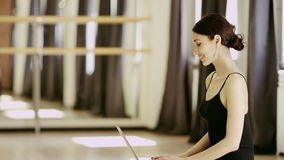 Beautiful girl wearing ballet leotard with laptop. Beautiful brunette girl wearing ballet leotard sitting in a beautiful pose on the floor with laptop indoor stock footage