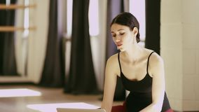 Beautiful girl wearing ballet leotard with laptop. Beautiful brunette girl wearing ballet leotard sitting in a beautiful pose on the floor with laptop indoor stock video footage