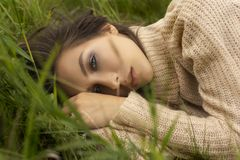 Beautiful girl wearing a beige sweater lays in a meadow among th. E green grass. Close-up portrait. Advertising, lifestyle, fashion and commercial design. Copy stock image