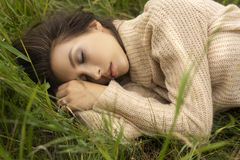 Beautiful girl wearing a beige sweater sleeps in a meadow among stock photography