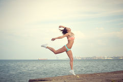 Beautiful girl wearing bikini in arabesque pose on Royalty Free Stock Images