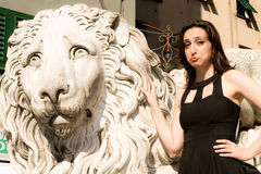 Beautiful girl wearing a black dress next to Gothic style lion statue  Royalty Free Stock Image
