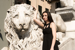 Beautiful girl wearing a black dress next to Gothic style lion statue  Royalty Free Stock Images