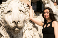 Beautiful girl wearing a black dress next to Gothic style lion statue  Stock Photography