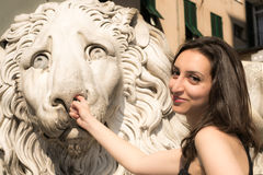 Beautiful girl wearing a black dress next to Gothic style lion statue picking his nose Royalty Free Stock Photos