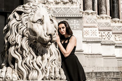 Beautiful girl wearing a black dress next to Gothic style lion statue  Royalty Free Stock Photos