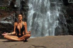 Beautiful girl wearing black one piece swimsuit meditating in lotus yoga pose stock photo