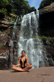 Beautiful girl wearing black one piece swimsuit meditating in lotus yoga pose Royalty Free Stock Image
