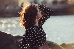 Beautiful girl wearing black polka dots dress enjoy summer sun on ocean beach at sunset time. Beautiful girl wearing black polka dots dress enjoy summer sun on royalty free stock photo