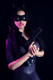 Beautiful girl wearing a catsuit holding a gun Stock Photography