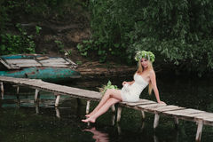 Beautiful girl wearing a crown sitting on a wooden bridge with a cat Stock Image