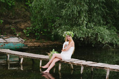Beautiful girl wearing a crown sitting on a wooden bridge with a cat Stock Images