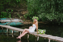 Beautiful girl wearing a crown sitting on a wooden bridge with a cat Royalty Free Stock Photos
