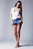Beautiful girl wearing denim shorts and shirt Stock Photography