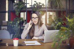 Beautiful girl wearing eye glasses in coworking studio talking by smartphone. Concept of young people working with mobile gadgets. Royalty Free Stock Image